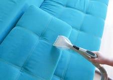 Sirva el sofá que limpia con la aspiradora, opinión del limpiador del hogar desde arriba Fotos de archivo libres de regalías