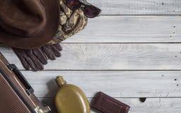 Sirva el sombrero del ` s y los accesorios retros para el viaje en un wo pintado blanco Fotografía de archivo libre de regalías
