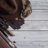 Sirva el sombrero del ` s y los accesorios retros para el viaje en un wo pintado blanco Foto de archivo libre de regalías