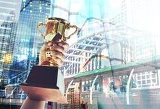 Sirva el soporte de una taza del trofeo del oro, concepto del triunfo imagenes de archivo