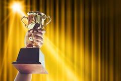 Sirva el soporte de una taza del trofeo del oro, concepto del triunfo fotos de archivo