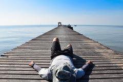 Sirva el sueño en el puente de madera al mar para relajarse Imagenes de archivo