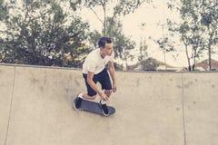 Sirva el tablero radical practicante del patín que salta y que disfruta de trucos y de trucos en pista patinadora del medio tubo  Foto de archivo