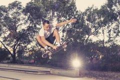 Sirva el tablero radical practicante del patín que salta y que disfruta de trucos y de trucos en pista patinadora del medio tubo  Fotografía de archivo
