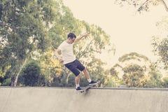 Sirva el tablero radical practicante del patín que salta y que disfruta de trucos y de trucos en pista patinadora del medio tubo  Foto de archivo libre de regalías