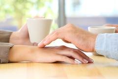Sirva el tacto de la mano de su socio durante una fecha Foto de archivo