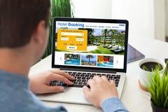 Sirva el teclado del ordenador portátil que mecanografía con el scre en línea del hotel de la reservación de la búsqueda fotografía de archivo