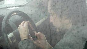 Sirva el teléfono móvil en el coche, imagen del uso de falta de definición de las fuertes lluvias en el camino almacen de video