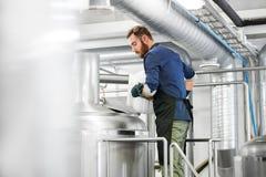 Sirva el trabajo en la cervecería del arte o la planta de la cerveza foto de archivo