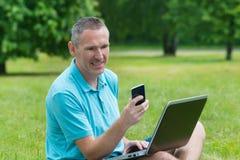 Sirva el trabajo en su computadora portátil en el parque Imágenes de archivo libres de regalías