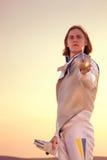 Sirva el traje de cercado blanco que lleva que se coloca punteagudo con su espada en la cámara y preparada para el duelo Foto de archivo libre de regalías