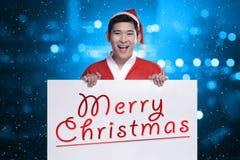 Sirva el traje de Papá Noel que lleva que sostiene la bandera con la escritura de la Feliz Navidad Foto de archivo libre de regalías