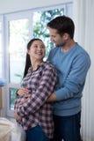 Sirva el vientre embarazada de la mujer conmovedora en la nueva casa Foto de archivo libre de regalías