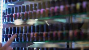 Sirva elegir el esmalte de uñas presente en tienda de belleza cerca del caso de demostración de la ventana, haciendo compras almacen de video