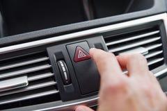 Sirva empujar el botón de la luz de emergencia mientras que conduce el coche Fotografía de archivo
