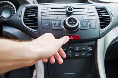 Sirva empujar el botón de la luz de emergencia mientras que conduce el coche Foto de archivo libre de regalías