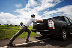 Sirva empujar un coche quebrado abajo del camino Fotografía de archivo libre de regalías