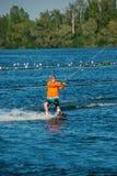 Sirva, en camisa anaranjada y el casco, está practicando wakeboarding imagen de archivo libre de regalías