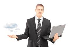 Sirva en un traje que sostiene un ordenador portátil y gersturing Fotos de archivo