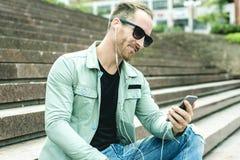 Sirva escuchar la música con auriculares de botón de a Imagen de archivo libre de regalías