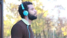 Sirva escuchar la música con los auriculares, gozando en naturaleza almacen de metraje de vídeo