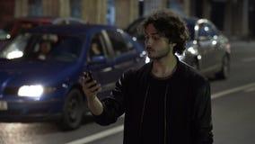 Sirva esperar y la comprobación de smartphone en la noche para saber si hay orden del coche de Uber en la calle urbana con tráfic almacen de metraje de vídeo