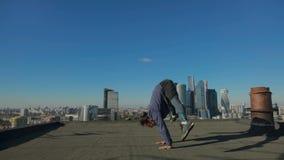 Sirva estirar en el tejado contra el contexto de la ciudad metrajes