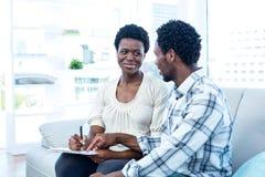 Sirva hablar con la esposa embarazada mientras que señala en el papel Fotografía de archivo