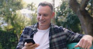 Sirva hablar en el teléfono móvil en el jardín 4k almacen de metraje de vídeo