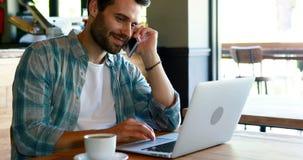Sirva hablar en el teléfono móvil mientras que usa el ordenador portátil almacen de metraje de vídeo