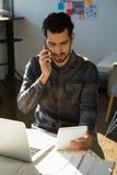 Sirva hablar en el teléfono móvil mientras que usa la tableta en la oficina Imagen de archivo