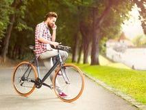 Sirva hablar en el teléfono que se sienta en la bicicleta imágenes de archivo libres de regalías