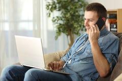 Sirva hablar en el teléfono y usar un ordenador portátil Fotos de archivo