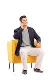 Sirva hablar en un teléfono asentado en una butaca moderna Fotos de archivo libres de regalías