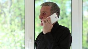 Sirva hablar en un teléfono celular con una mirada seria de la cara metrajes