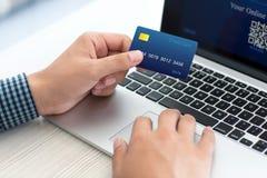 Sirva hacer compras en línea con la tarjeta de crédito en el ordenador portátil Foto de archivo libre de regalías