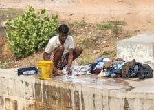 Sirva hacer el lavadero manualmente en el bloque de cemento de puente del río Imagen de archivo