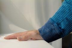Sirva inclinarse y pone sus manos abajo en el fondo blanco del paño Imágenes de archivo libres de regalías