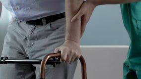 Sirva intentar hacer pasos mientras que se aferra al caminante, enfermera que lo apoya por el brazo metrajes