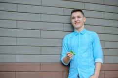 Sirva jugar con el hilandero verde al aire libre en el backgrou del ladrillo Fotos de archivo