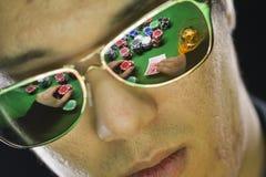 Sirva jugar el póker con la reflexión a través de sus gafas de sol Foto de archivo libre de regalías