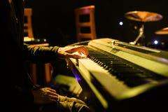 Sirva jugar en el teclado del sintetizador en etapa durante concierto Imagen de archivo libre de regalías