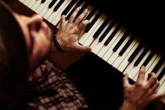 Sirva jugar en piano en etapa oscura dramática Imágenes de archivo libres de regalías