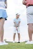 Sirva jugar a golf contra el cielo con los amigos que se colocan en primero plano Fotos de archivo libres de regalías
