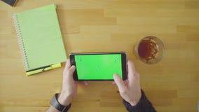 Sirva jugar a un juego en la tableta con la pantalla verde almacen de metraje de vídeo