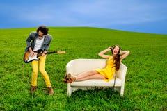 Sirva jugar un solo en la guitarra con la muchacha que miente en el sofá  Fotografía de archivo