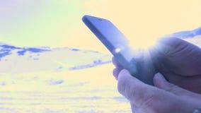 Sirva la búsqueda algo en smartphone en el pico de montaña El birlar con la mano en el teléfono móvil almacen de video