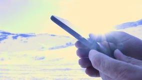 Sirva la búsqueda algo en smartphone en el pico de montaña El birlar con la mano en el teléfono móvil metrajes