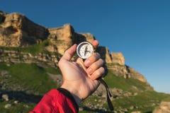 Sirva la búsqueda de la dirección con un compás en su mano en el punto de vista de las montañas del verano Búsqueda de la direcci fotografía de archivo