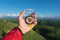 Sirva la búsqueda de la dirección con un compás en su mano en el punto de vista de las montañas del verano Búsqueda de la direcci fotos de archivo libres de regalías